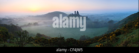 View towards Corfe Castle from West Hill on a misty sunrise. - Stock Photo