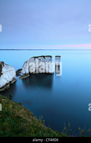 Old Harry Rocks, two chalk sea stacks located at Handfast Point, on the Isle of Purbeck at sunrise. - Stock Photo