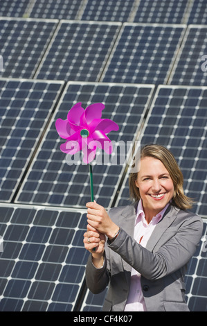 Germany, Munich, Woman holding paper windmill against solar panels, smiling, portrait - Stock Photo
