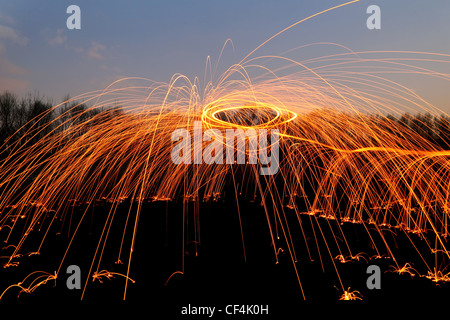 abstract background with orange sparklers flying away at night time outdoor - Stock Photo