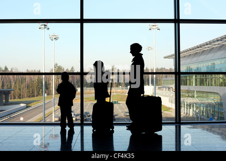 silhouette of mother, son and daughter with luggage standing near window in airport - Stock Photo