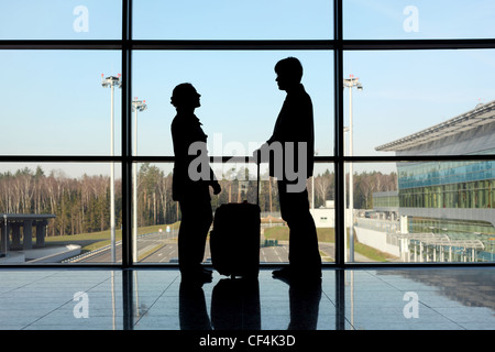 silhouette of man and girl with luggage standing near window in airport side view - Stock Photo