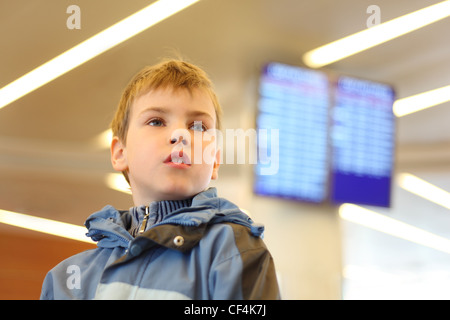 portrait of little boy in airport looking into the distance blue screens on background - Stock Photo