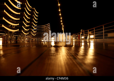 empty cruise ship deck with beach chairs and lamps at night time - Stock Photo