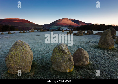 Castlerigg Stone Circle on a frosty morning while the first rays of light hit the slopes of Blencathra in the Lake - Stock Photo