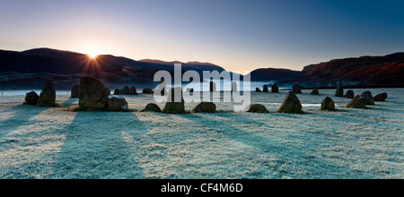 The Castlerigg Stone Circle on a frosty morning as the first rays of light appear over the hills in the Lake District. - Stock Photo