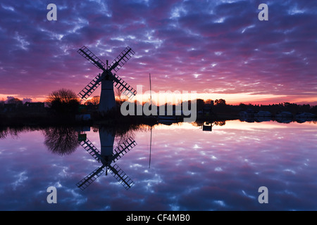 Thurne dyke drainage mill reflected in the River Thurne at sunrise on the Norfolk Broads. - Stock Photo