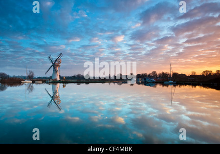 Thurne dyke drainage mill reflected in the River Thurne on the Norfolk Broads. - Stock Photo
