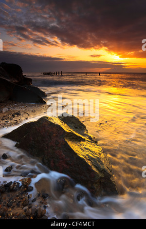 The sun shines through a break in the clouds at sunrise on the Norfolk coast. - Stock Photo