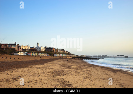 A view along the sandy beach at Southwold featuring the famous beach huts, lighthouse and pier. - Stock Photo