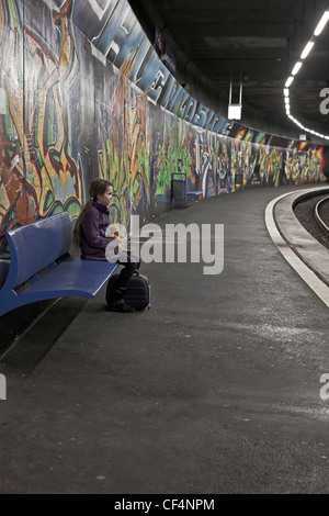Girl sitting with teddy bear and box on a bench in a subway station with graffiti and waits. - Stock Photo