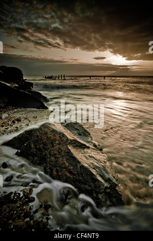 Sun breaking through the clouds during sunrise over large rocks on the beach at Happisburgh on the north-east coast - Stock Photo