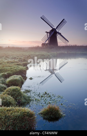 Herringfleet mill or Walker's Mill, a 19th century fully restored octagonal drainage mill reflected in the Broads - Stock Photo