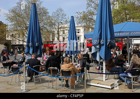 People sitting at tables at a pavement cafe on the King's Road in Chelsea. - Stock Photo