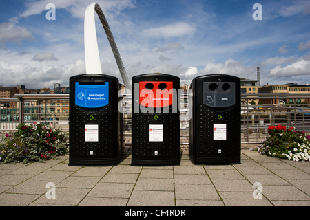 Recycling bins on the quayside in Gateshead with the Gateshead Millennium Bridge in the background. - Stock Photo