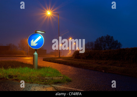 A road sign indicating to keep left, lit up at dusk. - Stock Photo