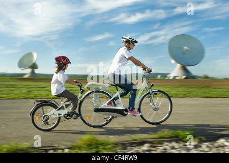 Germany, Bavaria, Raisting, Woman with girl riding electric bicycle near radio station - Stock Photo