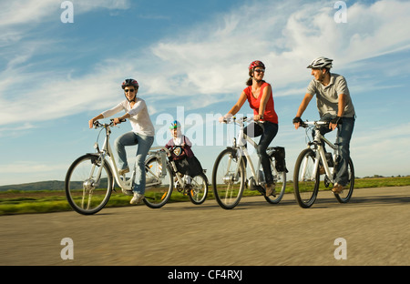 Germany, Bavaria, Raisting, People riding electric bicycle near radio station - Stock Photo