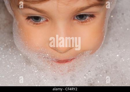 small child taking a bath, the head of foam. looks toward - Stock Photo