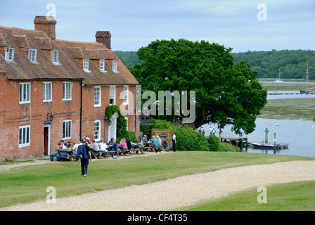 People sitting outside the Master Builder's pub in Buckler's Hard, a once important shipbuilding centre. Three ships - Stock Photo