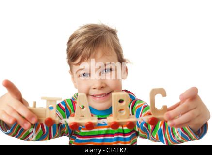 pretty little girl keeps in hands toy wooden steam locomotive with cars in form of alphabet letters isolated on - Stock Photo