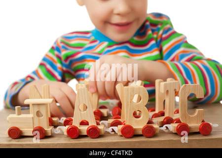pretty little girl played by toy wooden steam locomotive cars form alphabet letters isolated white background steam - Stock Photo