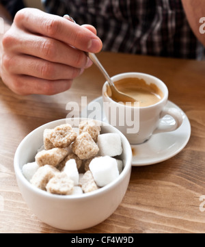 Detail of man's hand holding a spoon stirring a cup of espresso coffee, with a sugar bowl and sugar cubes in foreground. - Stock Photo