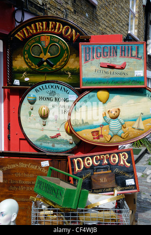 Lots of old hand painted wooden advertising signs for sale outside an antiques shop in Portobello Road. - Stock Photo