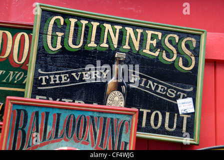An old wooden, hand painted Guinness advertising sign for sale ouside an antiques shop in Portobello Road. - Stock Photo