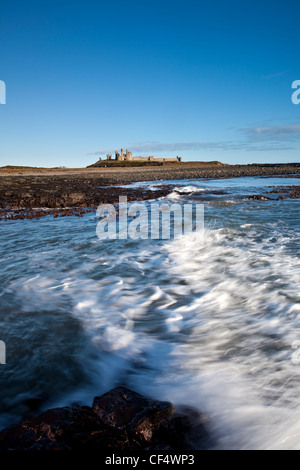 The remains of Dunstanburgh Castle built on a headland dominating a spectacular part of the Northumberland coast. - Stock Photo