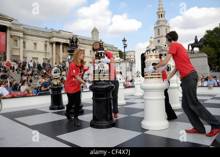 Helpers moving giant chess pieces handcrafted by Jaime Hayón during a game as part of The Tournament, an installation - Stock Photo