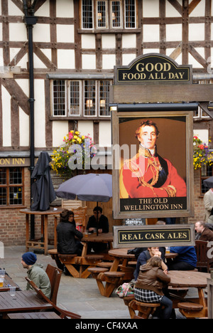 People sitting outside The Old Wellington Inn in New Cathedral Gate. The building which has existed since 1552 is - Stock Photo