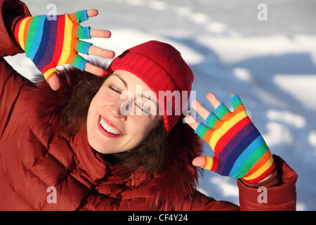 young beauty girl in multicolored mittens smiling and putting hands near face,eyes closed, outdoor at winter day - Stock Photo