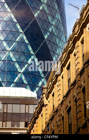 30 St Mary Axe known as the Gherkin, rising above buildings in the City of London. - Stock Photo