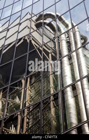 Lloyds of London building reflected in a glass clad office building in the City of London. - Stock Photo