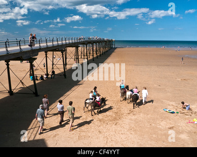 Donkey rides on the beach by the Victorian pier at Saltburn-By-The-Sea. - Stock Photo