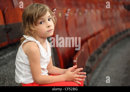 little girl sitting on stair near armchairs in circus and looking at camera - Stock Photo