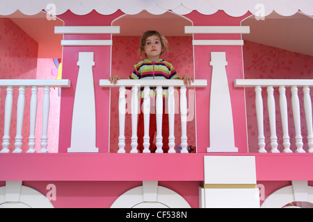 little girl standing on pink childish balcony and looking into the distance - Stock Photo