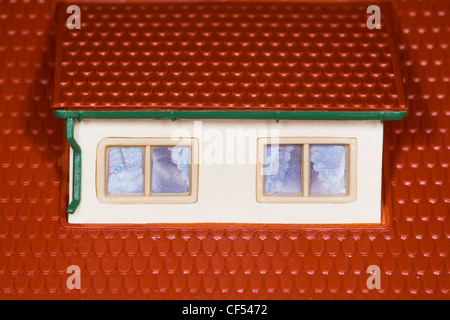 attic on roof of toy plastic house,two windows - Stock Photo