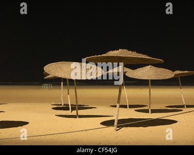 Morocco, Essaouira, Sunshades on beach at night - Stock Photo
