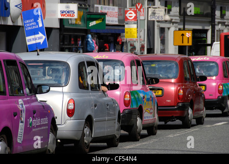 A queue of colourful London taxi cabs in Oxford Street. - Stock Photo