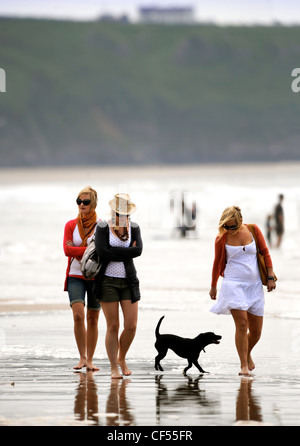 Three girls walk with their dog on a chilly spring day at Rhossili Bay on The Gower, South Wales UK - Stock Photo