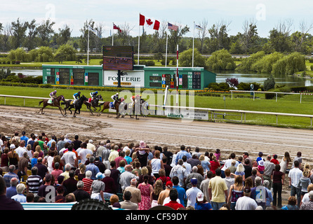 Canada, Ontario, Fort Erie, Crowd watching horse race finish at all weather dirt track. - Stock Photo