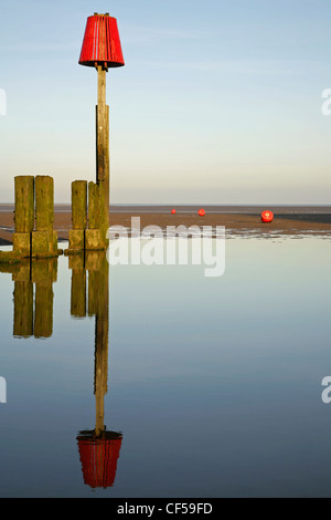 Navigation marker post and timber sea defence groyne at low tide. Cleethorpes, North East Lincolnshire, England - Stock Photo