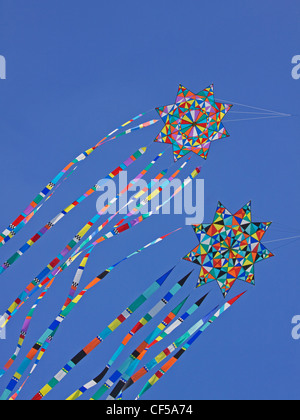 Colorful kites riding on the breeze against a clear blue sky