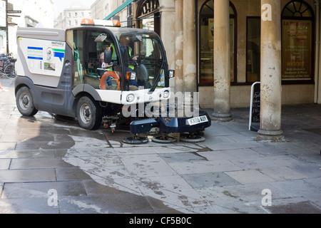 Street cleaning machine sweeping the pavement in Bath city centre, Somerset - Stock Photo