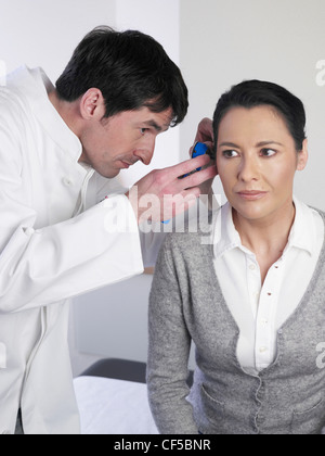 Germany, Hamburg, Doctor examining patient ear with medical equipment - Stock Photo