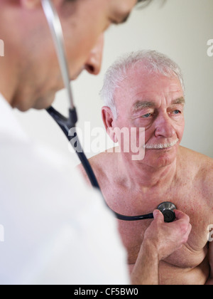 Germany, Hamburg, Doctor examining patient with stethoscope in clinic - Stock Photo