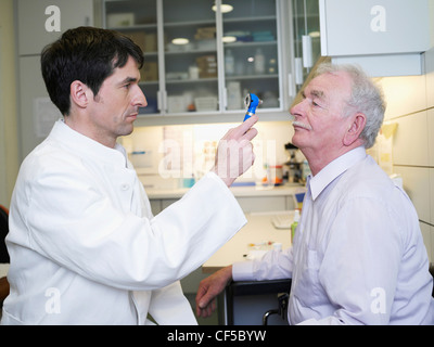 Germany, Hamburg, Doctor examining patient with otoscope in clinic - Stock Photo