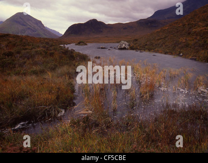 View of mountains during storm with small Lochan in foreground. - Stock Photo